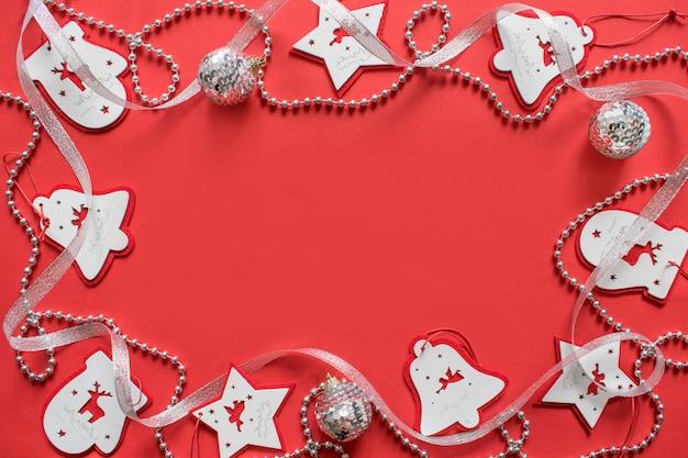 クリスマスの組成物、赤い背景のモックアップ。白と銀のリボン、花輪、おもちゃ