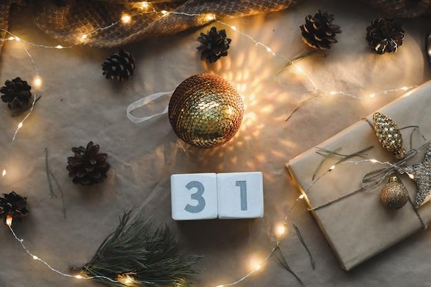 クリスマス作文。大晦日。トウヒの枝と輝く花輪のクラフト紙の背景にカレンダーの12月31日。新年の日付。フラットレイ、上面図