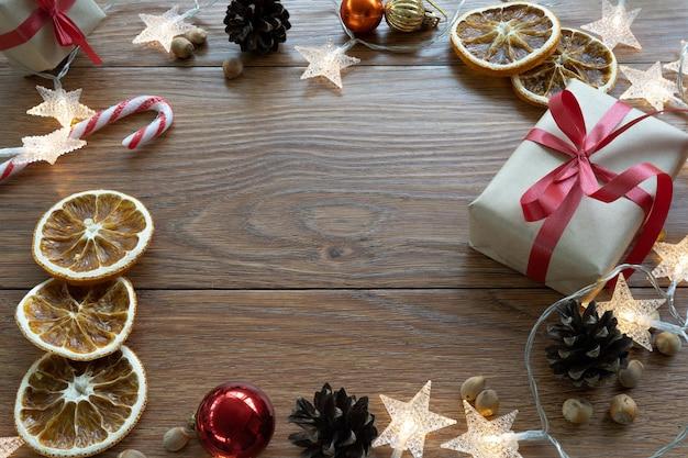 クリスマス作曲。暗い木製の背景に新年のレイアウト。コーン、おもちゃ、ギフト、花輪。
