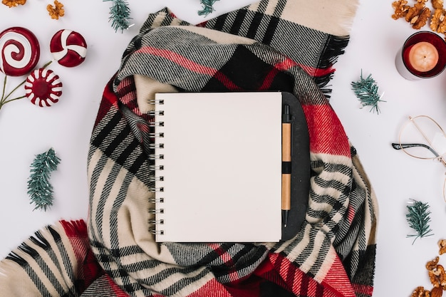 Christmas composition of notepad on scarf
