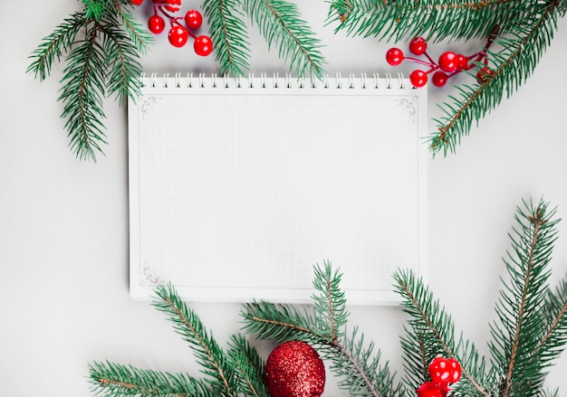 Christmas composition of notepad with fir tree branches