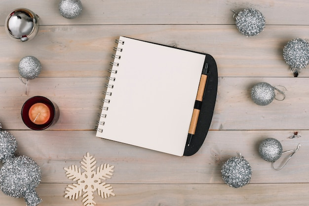 Christmas composition of notepad with silver baubles