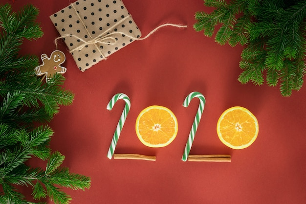 Christmas composition. number 2020 made of candy and half oranges. branches of spruce. christmas presents, winter, new year concept. flat lay, top view, copy space