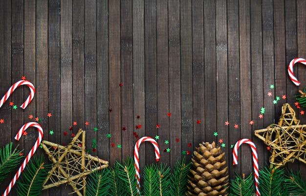 木の枝、サンタ帽子、キャンディー星、松ぼっくり、木製の新年の休日パターンのクリスマス組成。 copyspace。