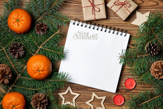 メリークリスマスの碑文と空白のメモ帳のクリスマスの構成