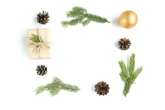 Новогодняя композиция из рождественских шаров, подарочной коробки, шишек и еловых веток, изолированных на белой поверхности. плоская планировка, вид сверху, копия пространства