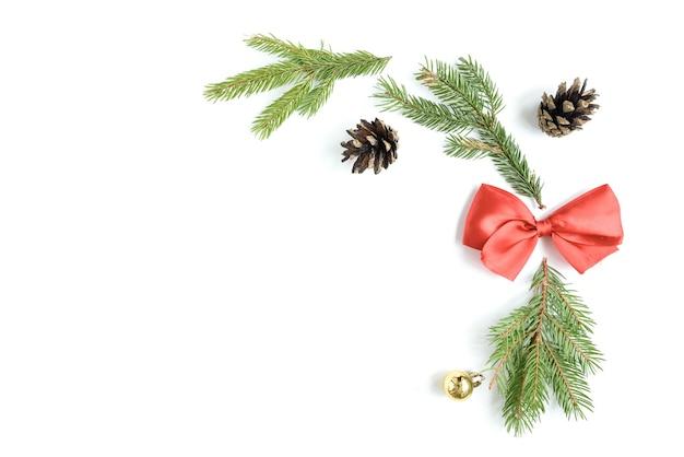 Рождественский состав елочных игрушек, шишек и еловых веток, изолированных на белой поверхности. плоская планировка, вид сверху, копия пространства