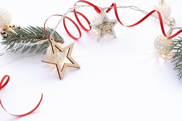 Рождественская композиция из еловых веток, деревянные звезды, гирлянды из белых светящихся шаров и красной лентой на белом фоне.
