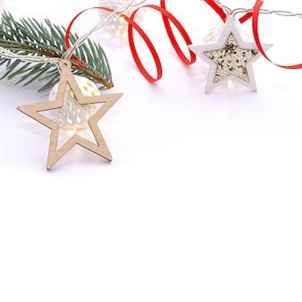 モミの枝、木製の星、白い発光球の花輪、白地に赤いリボンのクリスマス組成物。