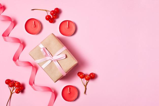 Новогодняя композиция из подарочной коробки со свечами, лентой и ягодами рябины с копией пространства