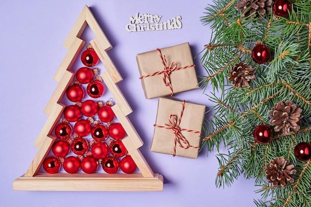 ギフトボックスと赤いクリスマスボールが中にある木製のクリスマスツリーのクリスマスの構成