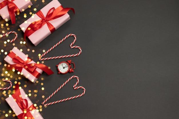赤いリボンの装飾、キャンディー杖、時計、暗闇の上のゴールドのキラキラキャンディーとギフトボックスのクリスマス組成