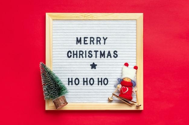Рождественская композиция из девушки-лыжницы, дерева, белой фетровой доски на красном фоне