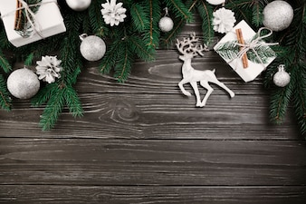Christmas composition of green fir tree branches with small deer