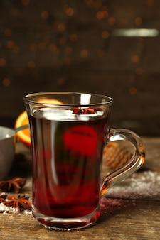 木製のテーブルにグリューワイン、シナモン、シチュー鍋のクリスマスの構成