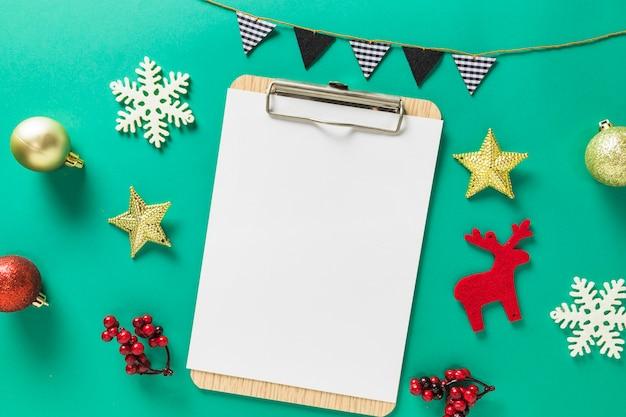 小さなおもちゃとクリップボード上の紙のクリスマスの組成