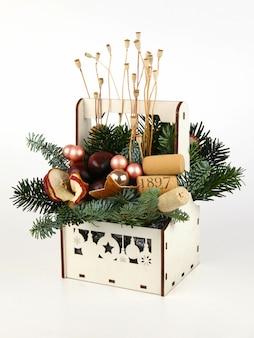 Новогодняя композиция из сосновых веток, винных пробок, шариков, сушеных дольок яблока, мака и каштанов. в деревянном ящике белого цвета. на белом фоне