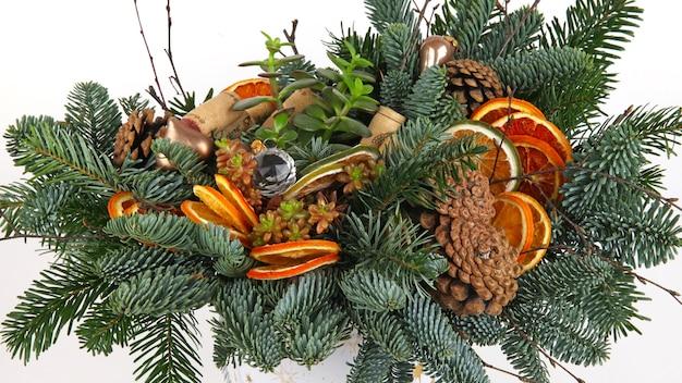 Новогодняя композиция из сосновых веток, винных пробок, шариков, сушеных дольок апельсина и сосновых шишек. крупным планом выстрел. на белом фоне