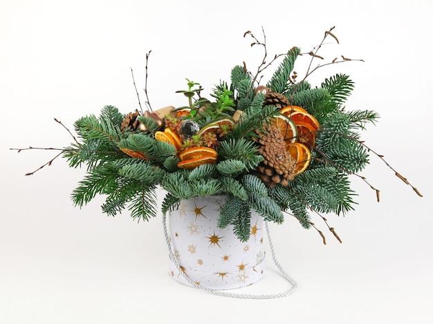 Новогодняя композиция из сосновых веток, винных пробок, шариков, сушеных дольок апельсина и сосновых шишек. в белом ведре. на белом фоне