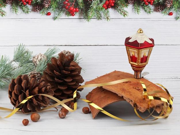 松ぼっくり、ランタン、ヘーゼルナッツ、木の樹皮と松の木の枝の明るい木の表面とモミの境界線のある背景のクリスマスの構成