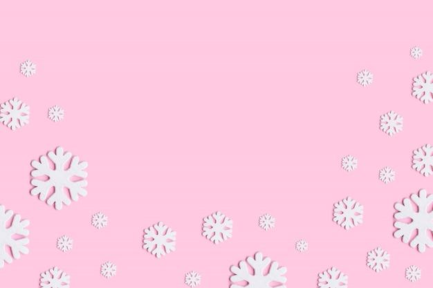 Рождественская композиция из снежинок на пастельных розовом фоне.