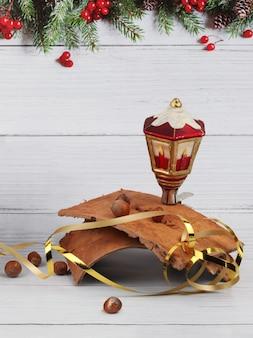 おもちゃのランタン、きらびやかなヘーゼルナッツ、木の樹皮のクリスマスの構成は、明るい木の表面とモミの境界線のある背景にあります。コピースペース付き