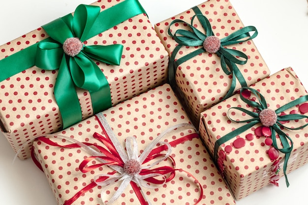 Рождественская композиция из различных подарочных коробок, завернутых в крафт-бумагу и украшенных атласными лентами вид сверху, плоская планировка.