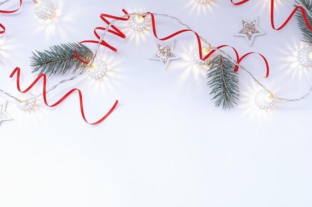Рождественская композиция из белых блестящих звезд, гирлянда из белых светящихся шаров, красные ленты и еловые ветки на белом фоне.