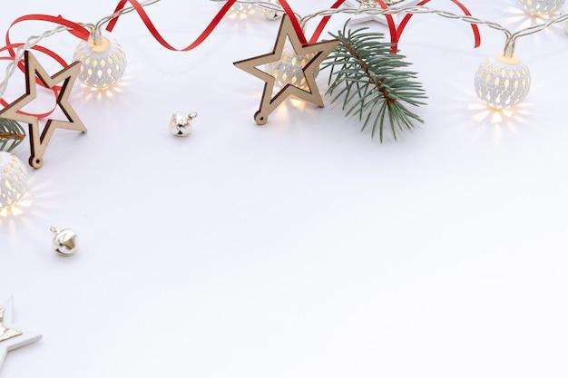 Рождественская композиция из деревянных звезд, гирлянда из белых светящихся шаров, еловые ветки, колокольчики и красная лента на белом фоне.