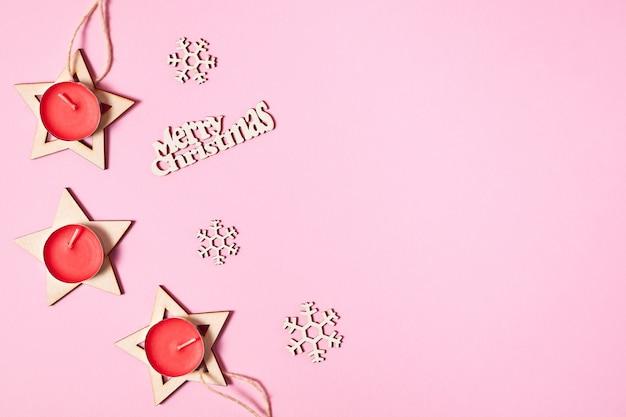 Новогодняя композиция из деревянных звезд, красных свечей и снежинок на розовом бумажном фоне