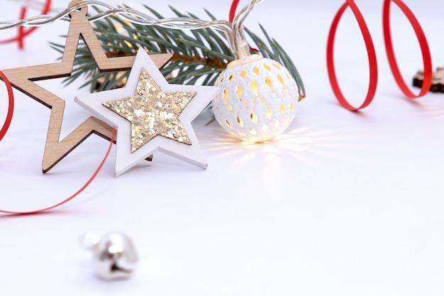 Рождественская композиция из деревянных звезд с блестками, гирлянды из белых светящихся шаров, еловые ветки и красные ленточки на белом фоне.