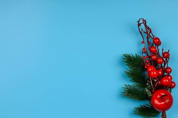Новогодняя композиция на синем фоне. ветвь рождественской елки с шишками и красными ягодами. креативная концепция. плоский стиль, вид сверху.
