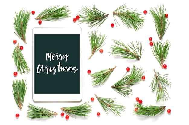 白い背景の上のクリスマスの構成。メリークリスマス-ガジェット画面の手書きの碑文。フラットレイ。