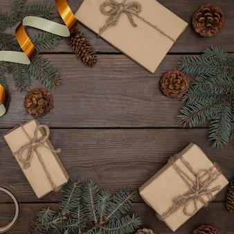 木製のテーブルの上のクリスマスの構成、ギフト、クリスマスツリーの円錐形、お祝いのリボン、上面図。