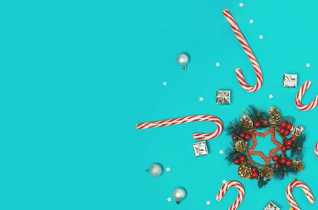 青い背景の上のクリスマスの構成。キャンディケイン、赤い果実とクリスマスフレーム。上面図