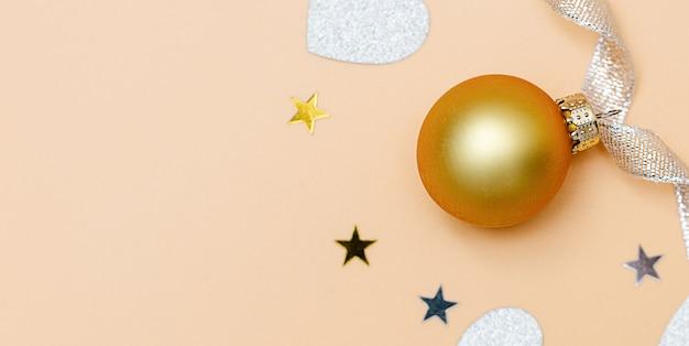 パステルオレンジ色の背景にクリスマスの構成。クリスマス、冬、新年のコンセプト。
