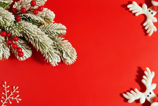 Новогодняя композиция на красном фоне из снежного дерева с красными ягодами и декоративными оленями. плоская планировка, вид сверху, копия пространства.