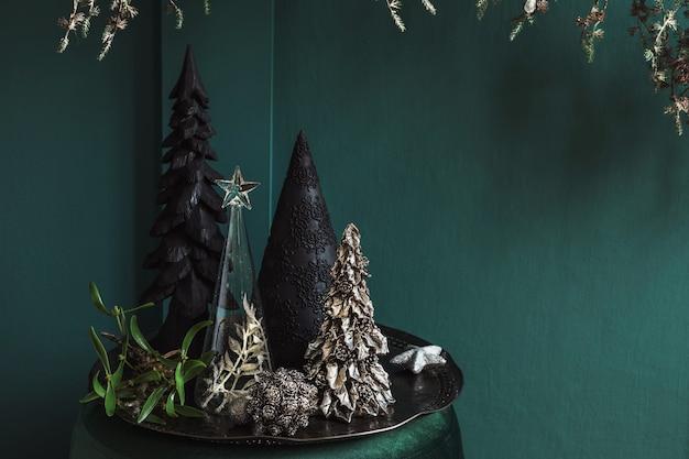 居間の緑のビロードのプーフのクリスマスの構成。美しい装飾。クリスマスツリー、キャンドル、星、ライト、エレガントなアクセサリー。メリークリスマスとハッピーホリデー、テンプレート。