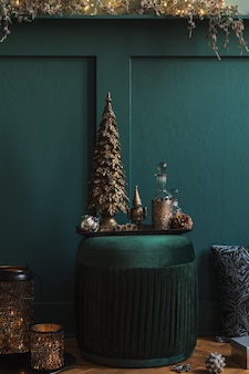 Новогодняя композиция на зеленом бархатном пуфе в гостиной. красивое украшение. новогодние елки, свечи, звезды, огоньки и изящные аксессуары. веселого рождества и счастливых праздников, шаблон.