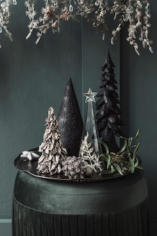 リビングルームの緑のビロードのプーフのクリスマスの構成。美しい装飾。クリスマスツリー、キャンドル、星、ライト、エレガントなアクセサリー。メリークリスマスとハッピーホリデー、テンプレート。