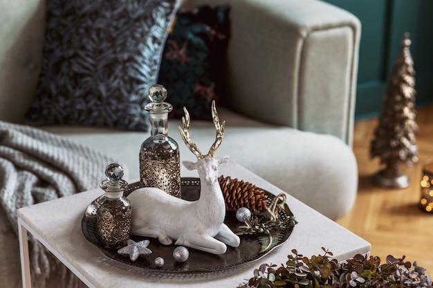 Новогодняя композиция на мраморном столе в интерьере гостиной с красивым декором. елка, олени, свечи, звездочки, легкие и нарядные аксессуары. шаблон. счастливого рождества.