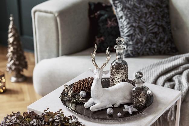 美しい装飾が施されたリビングルームのインテリアの大理石のテーブルのクリスマスの構成。クリスマスツリー、鹿、キャンドル、星、軽くてエレガントなアクセサリー。レンプレート。メリークリスマス。