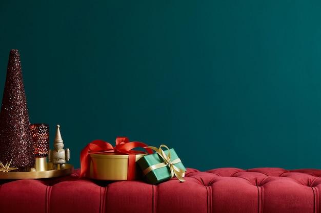 Новогодняя композиция на красной бархатной скамейке с украшениями, подарками, венком, фонарем и аксессуарами. скопируйте пространство. красный и зеленый цвет. шаблон.
