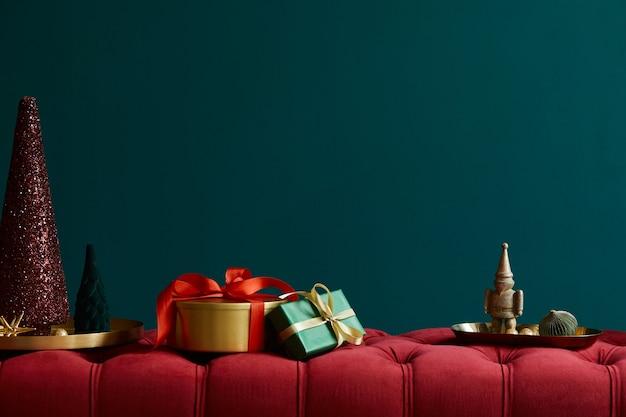 装飾、ギフト、花輪、ランタン、アクセサリーが付いた赤いベルベットのベンチでのクリスマスの作曲。スペースをコピーします。赤と緑の色。レンプレート。