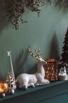 Новогодняя композиция на полке в интерьере гостиной. красивое украшение. елки, свечи, звездочки, легкие и нарядные аксессуары. веселого рождества и счастливых праздников, шаблон.