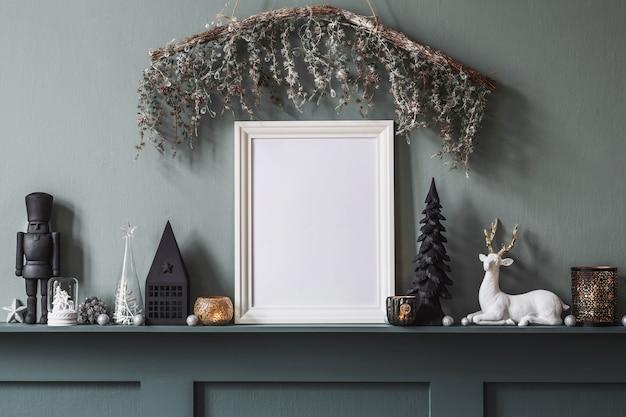 美しい装飾とモックアップポスターフレームを備えたリビングルームのインテリアの棚の上のクリスマスの構成。クリスマスツリー、鹿、キャンドル、星、軽くてエレガントなアクセサリー。レンプレート。