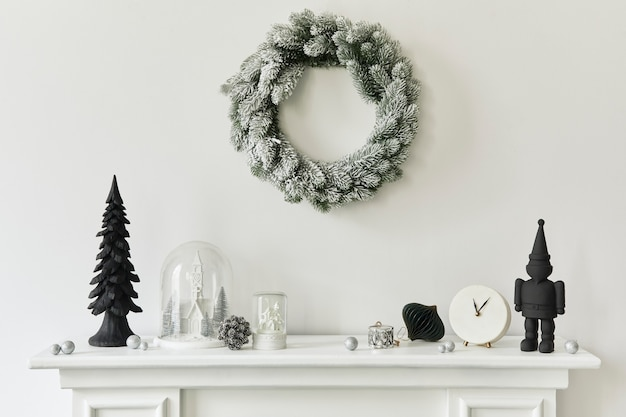 Новогодняя композиция на белом дымоходе в интерьере гостиной с красивым декором. елка и венок, свечи, звезды, свет. скопируйте пространство. шаблон.