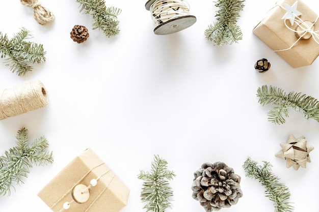 白い表面のクリスマスの構成。手作りのギフトボックス、クリスマスの飾り、モミの枝、松ぼっくり。手作りのdiyコンセプト。フラットレイ、上面図、コピースペース