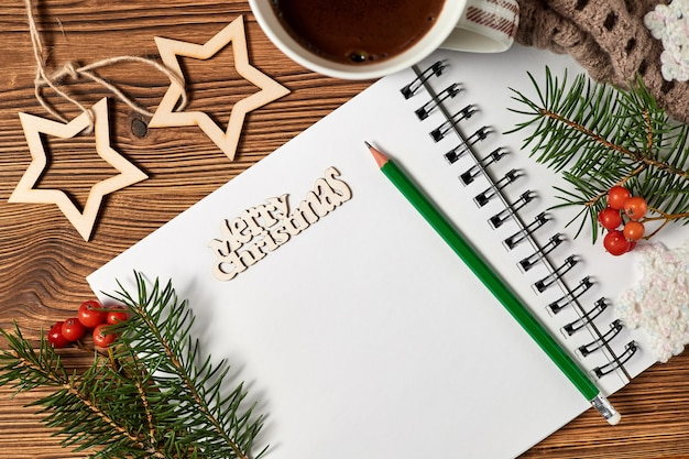 Christmas composition of open blank notepad, coffee cup, scarf and fir branches on wooden background