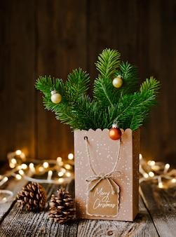 크리스마스 구성. 종이 봉투와 함께 전나무 가지 갈색 나무 배경 및 bokeh 빛 범프.